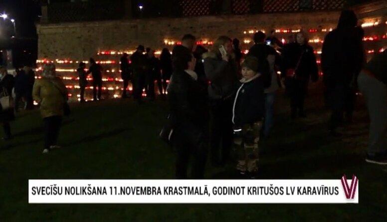 Cilvēki noliek svecītes pie Rīgas pils mūra, godinot kritušos karavīrus