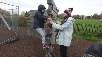 Magone ar bērniem spēlējas rotaļlaukumā Anglijā