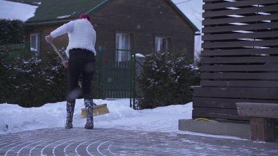 Mamma tīra sniegu, kamēr vīrs stāv malā